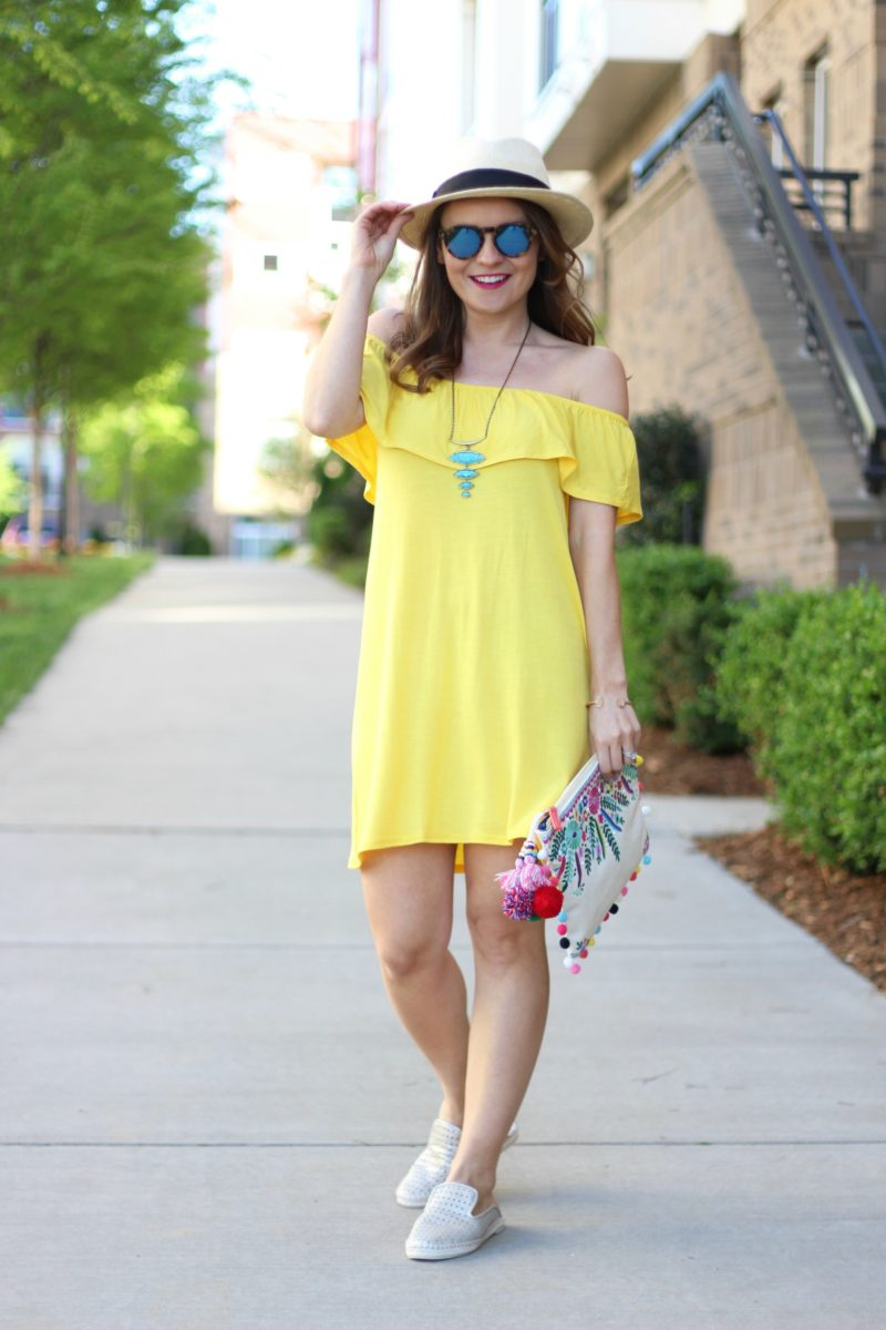 yellow off the shoulder ruffle dress, pom pom clutch